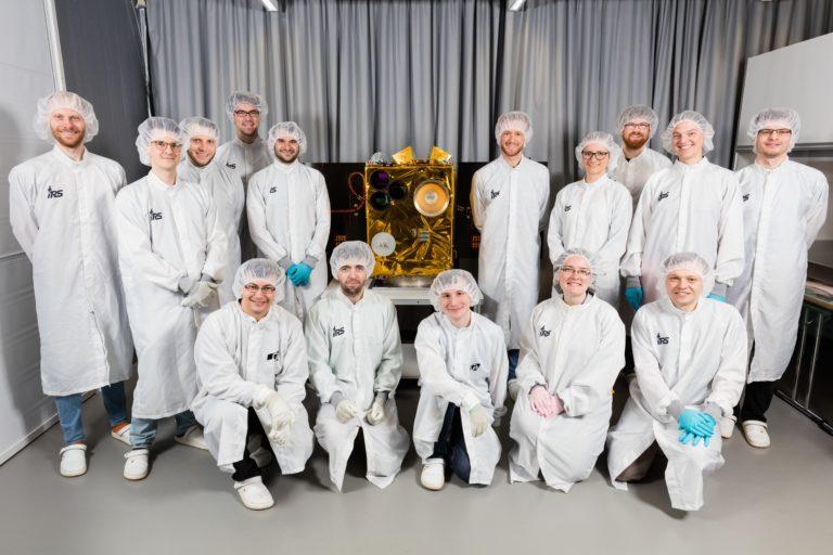 """Das Team der Uni Stuttgart mit dem eigenen Satelliten """"Flying Laptop"""". Foto: Universität Stuttgart"""