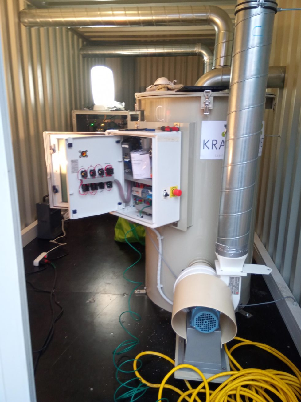 Ein Blick in den Container, der Straßenluft von Stickoxiden befreit, in Heilbronn. Ein Motor (vorne im Bild) saugt Straßenluft von der rechten Containerseite in den zylinderförmigen Aufbau. Dieser enthält das spezielle Aluminiumsilikat, an das die Stickoxide binden. Der Schaltschrank mit dem Bedienpanel ist geöffnet, die Stickoxid-Analytik steht weiter hinten. Die gereinigte Abluft wird durch das Rohr (vorne im Bild) nach draußen geleitet. Foto: Alexander Krajete