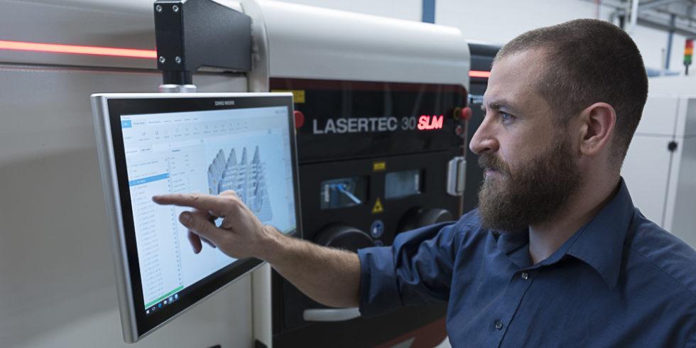 Mann bearbeitet CAD-Daten am Bildschirm eines 3D-Druckers