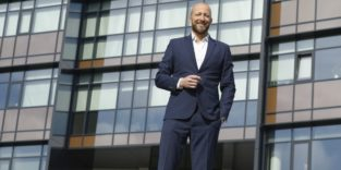 Prof. Johannes Henrich Schleifenbaum, Director Additive Manufacturing and Functional Layers am Fraunhofer ILT in Aachen, vor einem Universitätsgebäude