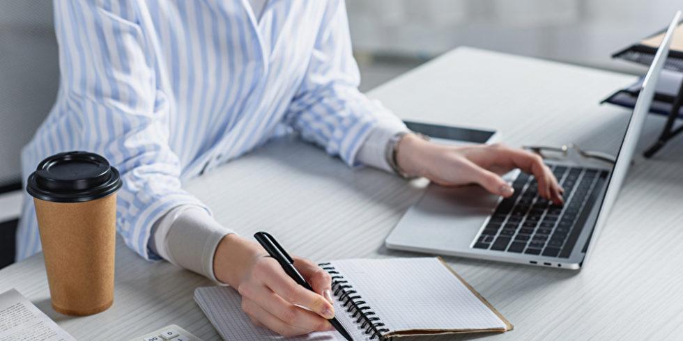 Frau lernt zuhause mit Laptop Schreibblock