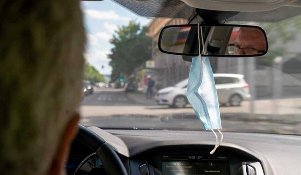 Maske hängt am Spiegel im Auto