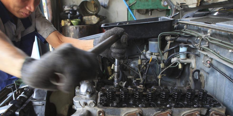 Mann beugt sich über Diesel-Motorblock