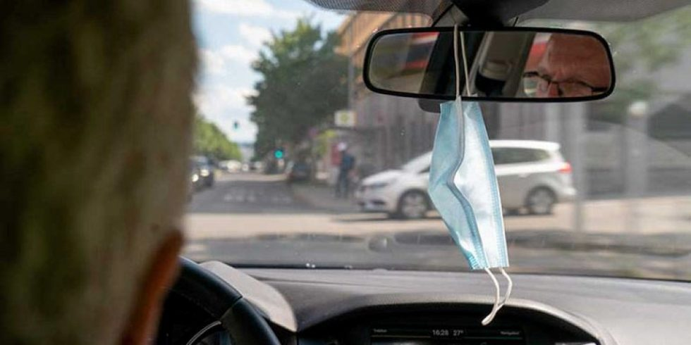 Um sie bei Bedarf schnell griffbereit zu haben, hängen viele ihre Corona-Schutzmasken an den Rückspiegel im Fahrzeug. Dort behindern sie die Sicht des Fahrers. Bild: © DEKRA / Thomas Küppers