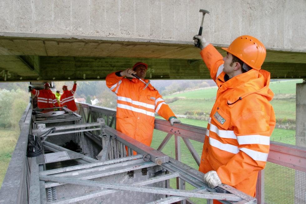 Brückenprüfer mit Hammer unter Brücke