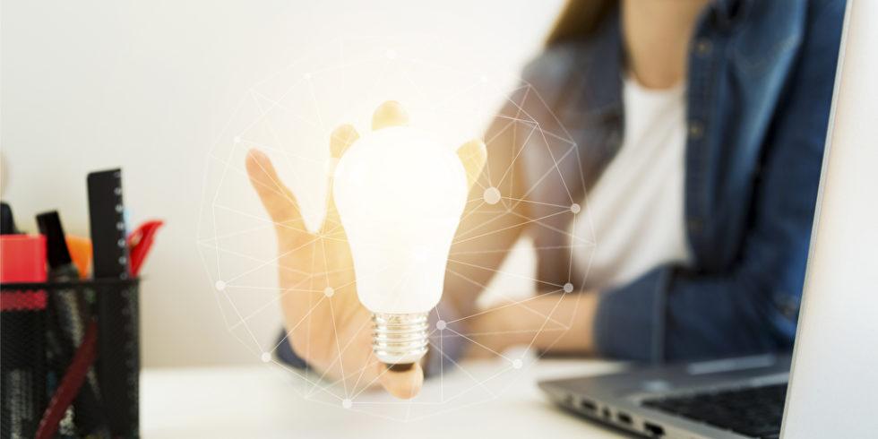 Frau mit Glühbirne am Schreibtisch
