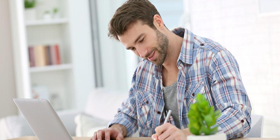 Mann vor Laptop schreibt