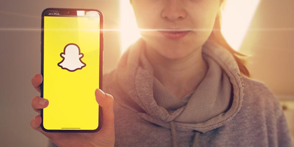 Snapchat auf dem Handy Frau hält es im Hintergrund