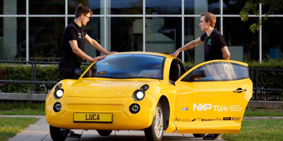 Zwei junge Männer stehen am gelben E-Auto Luca