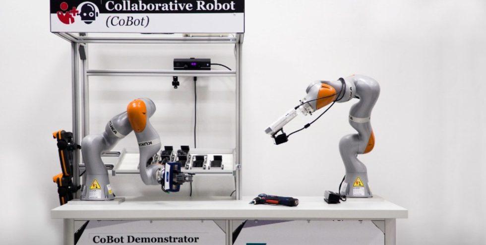 Bild 1. Der Montagetisch-Demonstrator mit zwei Roboterarmen und hinter der oberen Blende versteckter Kamera-/Projektor-Einheit.  Bild: Fraunhofer IOSB