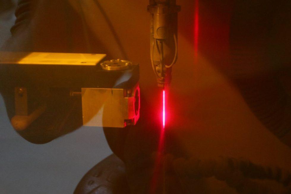 Die Qualität der Düsenöffnung wird beim LMJ-Laser indirekt durch Analyse der Raman-Strahlung erfasst. Links der Sensor, rechts der durch das Laserschutzfenster rot erscheinende LMJ-Strahl. Foto: Synova