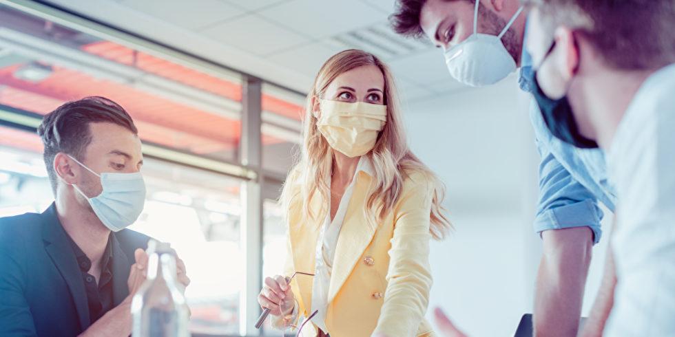 Leute mit Maske im Büro