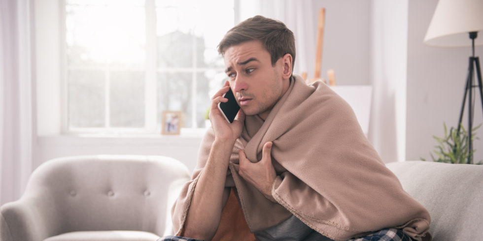 Mann krank in Decke am Telefon