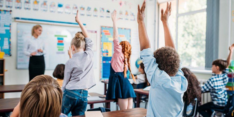 Klassenzimmer Schüler zeigen auf