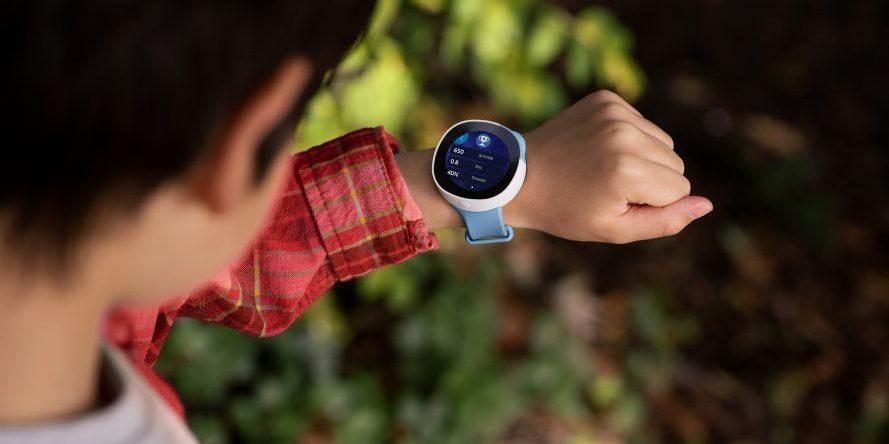 Kind schaut auf Handgelenk mit Smartwatch