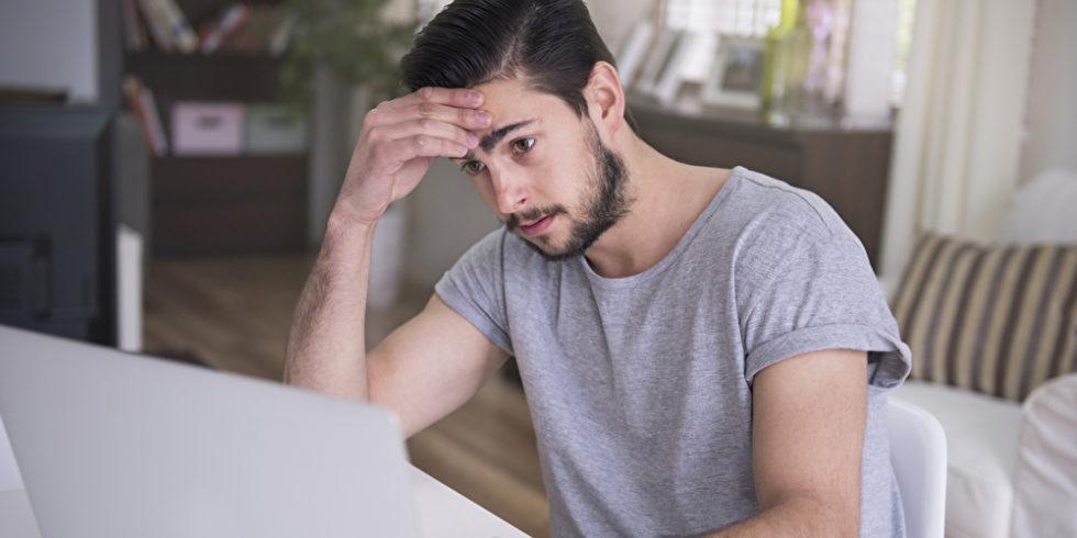 Mann schaut sorgenvoll in den Laptop