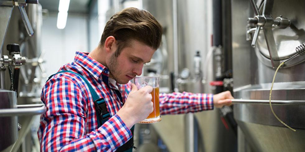 Mann in Karohemd testet Bier