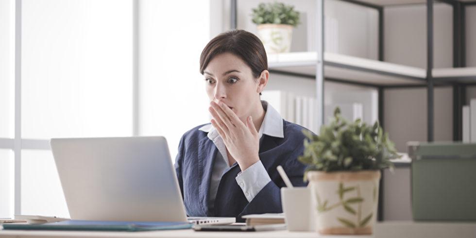 Frau sitzt erschrocken vor dem Bildschirm