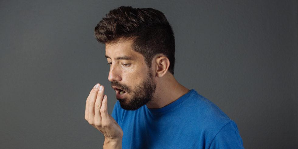 Mann riecht an seinem Atem