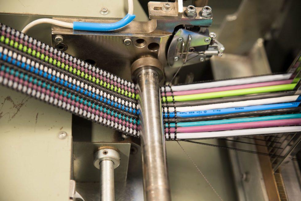 Gewebebandkabel: Während elektrische Leitungen, dünne Rundkabel oder Schläuche wie Kettfäden in Längsrichtung verlaufen, lassen textile Garne quer dazu ein Gewebe entstehen. Foto: TKD Kabel