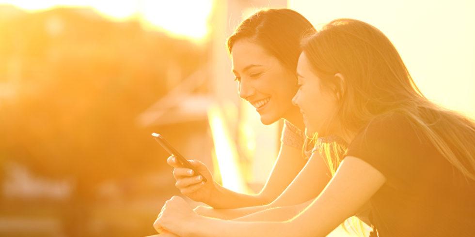Zwei Frauen schauen aufs Handy