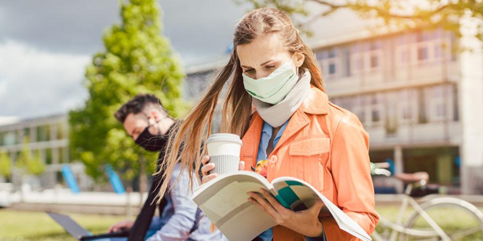 Studentin mit Maske und Büchern