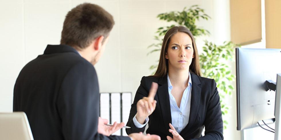 Boss und Angestellte am Schreibtisch, sie zeigt ablehnende Haltung