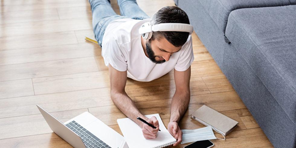Junger Mann lernt im Home Office liegend auf Boden vor Coach