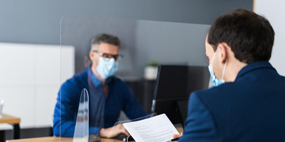 Zwei Männer sitzen mit Maske im Büro mit Plexiglas