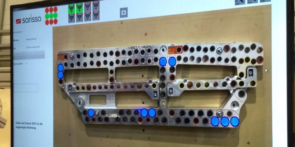 """Bild 1. Schablone mit blau angezeigten Bohrpositionen im digitalen Assistenzsystem. Am Flugzeugrumpf übernimmt dann die """"intelligente Maschine"""" den eigentlichen Bohrprozess. Foto: IPMT Hamburg"""