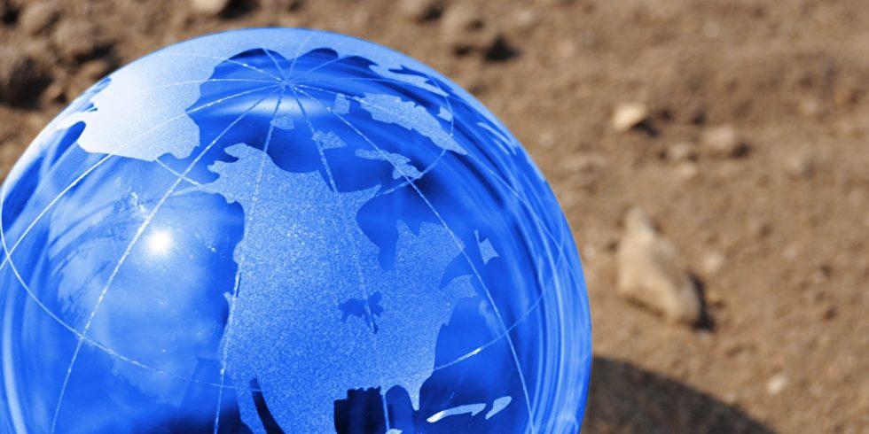 Blaue Weltkugel auf Sand