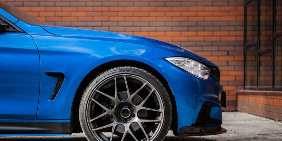 Blauer BMW parkt an Wand