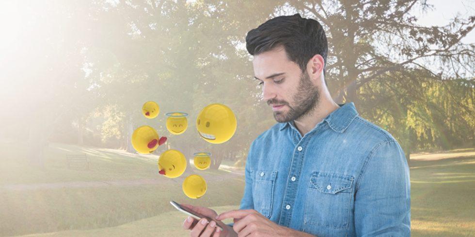 Mann schaut aufs Handy Emojis erscheinen