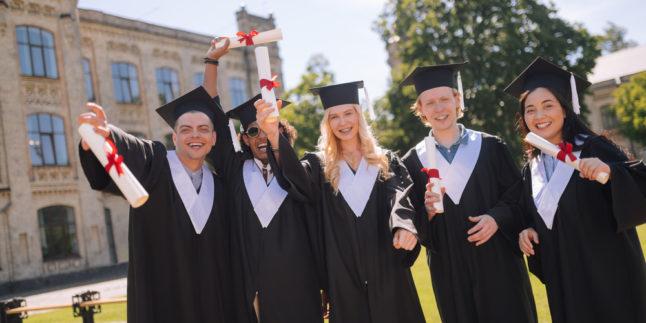 Studierende Abschluss stehen draußen mit Urkunde