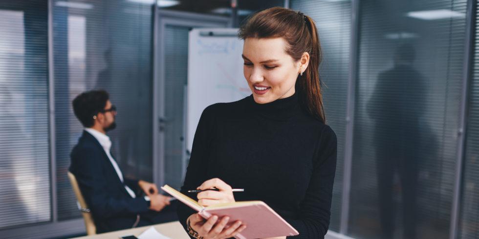 Frau Wirtschaftsingenieurin im Vordergrund schaut auf Tablet im Hintergrund sitzt Kollege