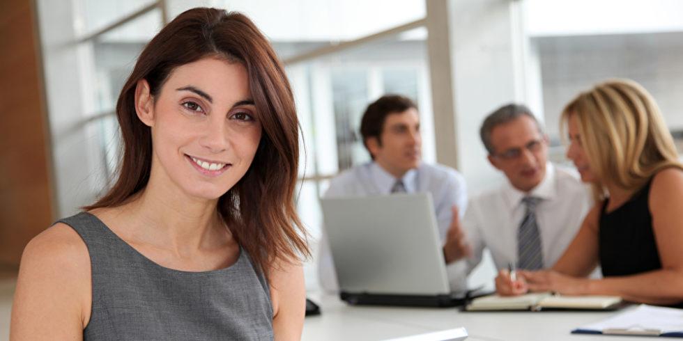Frau im Vordergrund mit Tablet im Hintergrund andere Kollegen