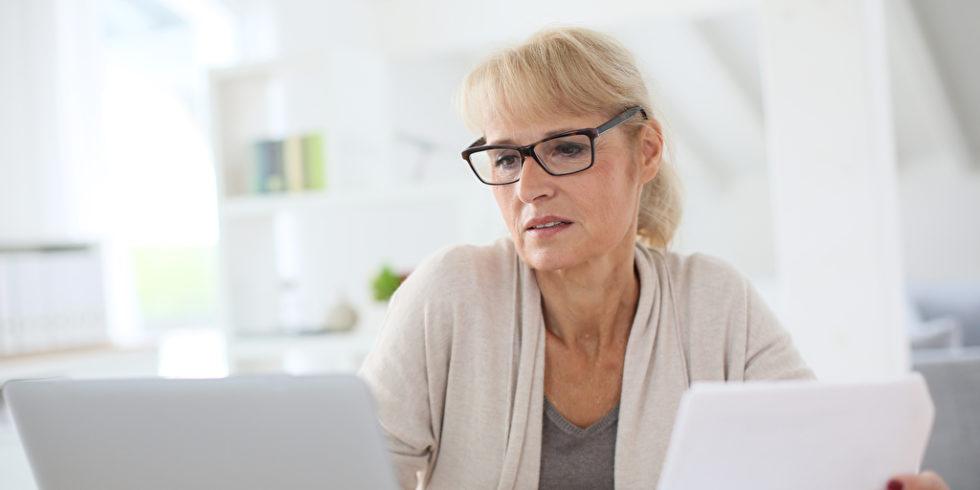 Frau am Laptop mit Papier
