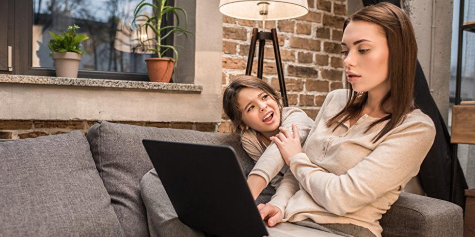Frau mit Laptop auf Sofa und Kind im Hintergrund