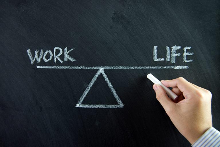 Tafel auf der Work Life steht mit Waage als Symbol Hand mit Kreide