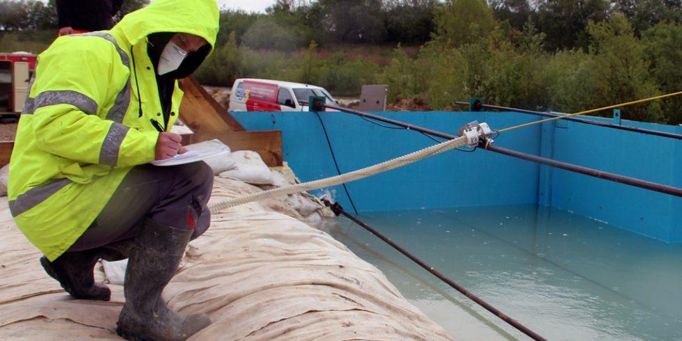 Im Großversuch wird das Container geflutet und der Deich getestet. Stefan Langer notiert dabei den Wasserstand. Foto: TH OWL/Pia Schlegel
