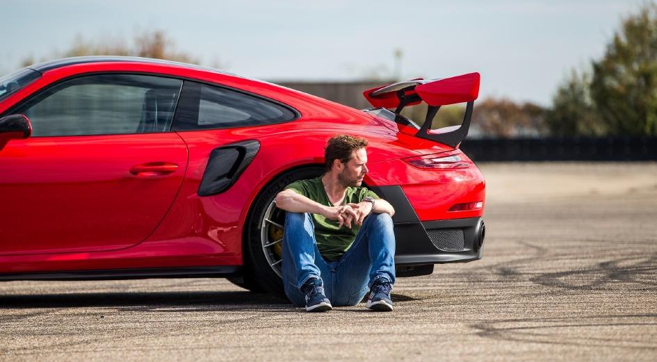 Alexander Bloch sitzt vor rotem Sportwagen