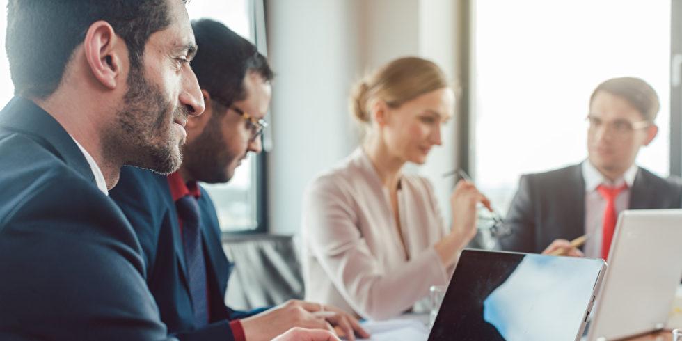 Business-Leute im Gespräch am Konferenztisch mit Laptop