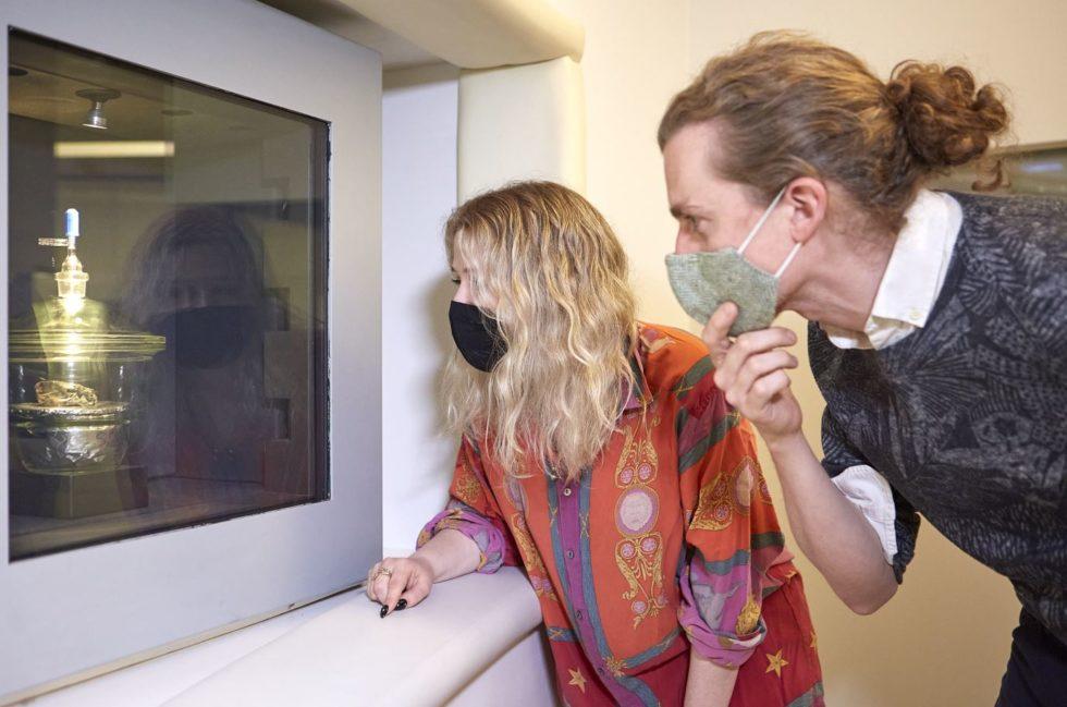 Mann und Frau vor Scheibe dahinter Meteorit ausgestellt
