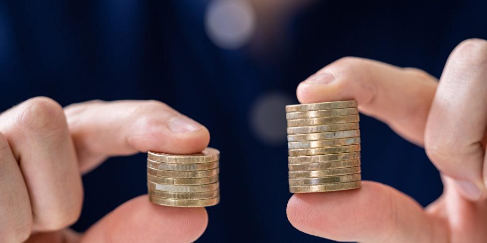 Mann hält zwei unterschiedliche Geldstapel