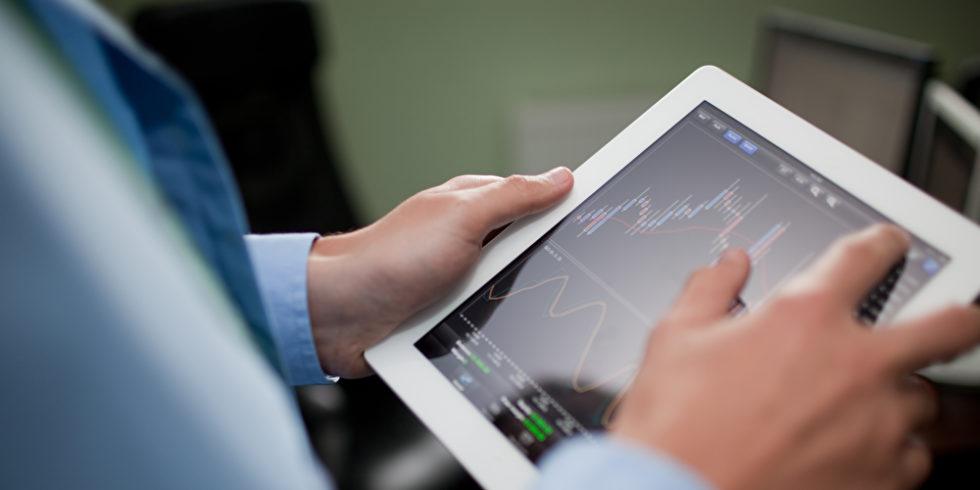 Mann checkt Börse auf Tablet