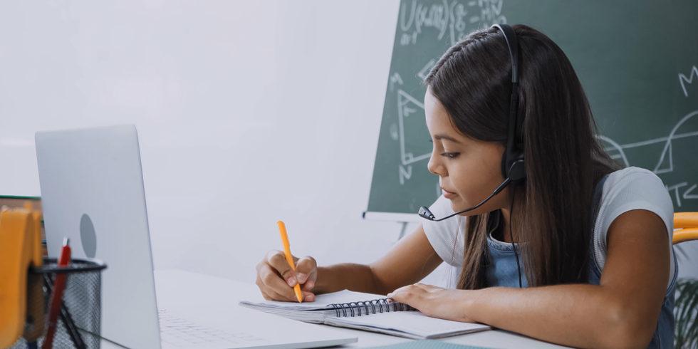 Schülerin mit Headset und Laptop