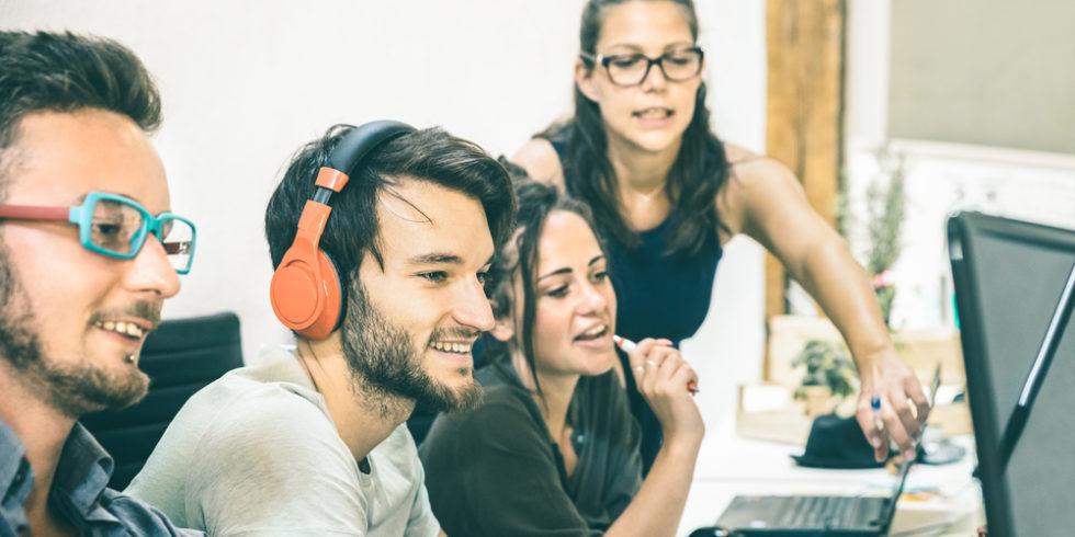 Junge Leute zusammen in einem Raum am Computer