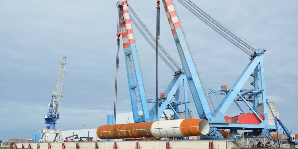 Ein Monopile wird im Steelwinds Hafen von Nordenham verladen. Er wiegt 1450 t, ist 83 m lang und hat einen Durchmesser von 8 m. Die rostbraunen Teile sind unbeschichtete Stahl-Oberflächen, die hellen korrosionsschutzbeschichtete Flächen. Foto: Ralf Hubo
