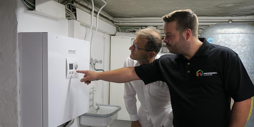 Heizungsfachmann Marcel Medding erläutert dem Betreiber die intuitive Bedienung: Zwei Taster und ein Handrad genügen, um die Wärmepumpe zu regeln. Foto: August Brötje GmbH
