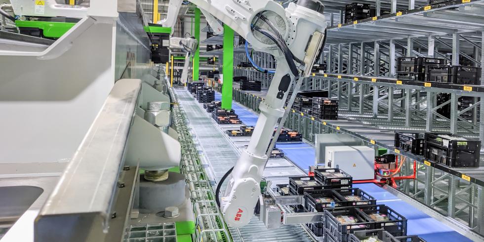 In der Kommissionierzone nehmen sechs auf einer Schiene positionierte sechsachsige IRB 6700-Roboter die Kisten auf und stellen diese in die für diesen Supermarkt vorgesehenen Sortierfächer. Foto: Heemskerk/ABB